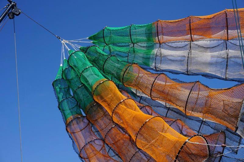 De fuiken hangen aan de mast van een vissersboot in de haven van Ouddorp