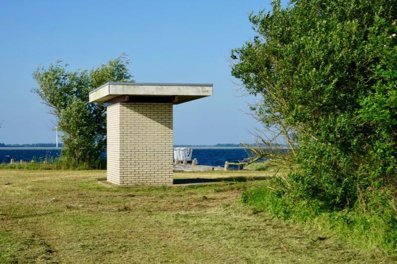 Het toilet met op de achtergrond de vuilcontainers op Mosselbank