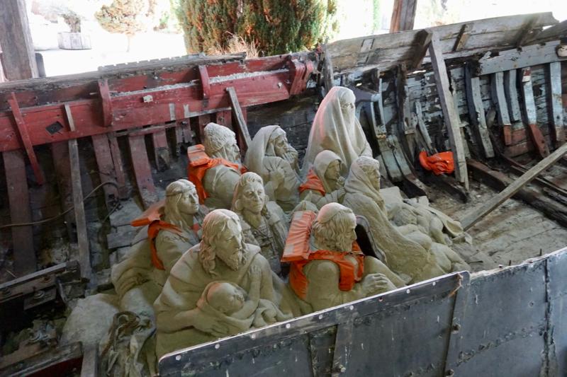 Oude botter met vluchtelingen bij de ingang van 'Zandsculpturen in Elburg'